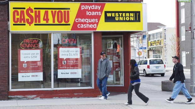 People walk pass a pay day loan store in Oshawa, Ont., May 13, 2017. THE CANADIAN PRESS