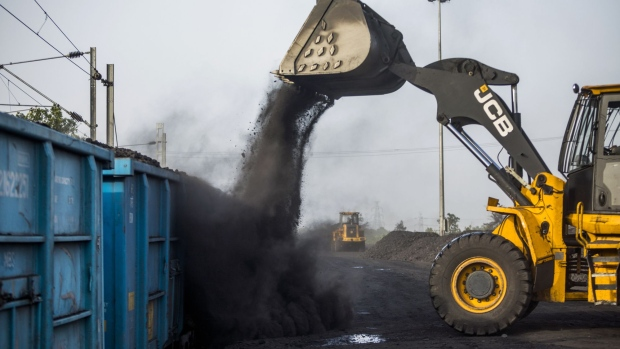 A JC Bamford Excavators Ltd. (JCB) front loader loads coal onto a freight wagon at the Tori Siding on the Tori-Shivpur rail line, operated by Indian Railways and funded by Coal India Ltd., in Chandwa, Jharkhand, India, on Thursday, May 17, 2018. State miner Coal India's output and shipments jumped to seasonal records in June, buoyed by summer demand from power stations, the company's biggest customers. Photographer: Prashanth Vishwanathan/Bloomberg