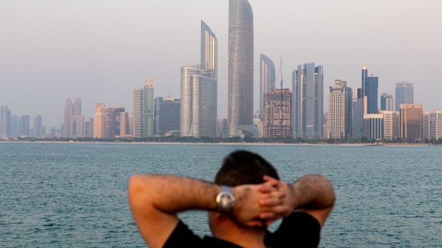 A visitor looks at the view of the city skyline from a breakwater in Abu Dhabi Photographer: Christopher Pike/Bloomberg