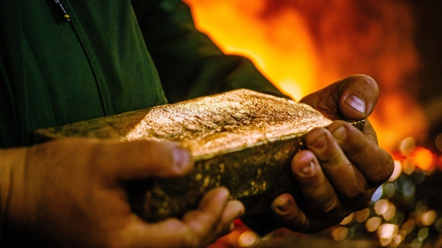 A worker carries a 28 kilogram gold bar after casting and cleaning in the foundry at the South Deep gold mine, operated by Gold Fields Ltd., in Westonaria, South Africa. Photographer: Waldo Swiegers/Bloomberg