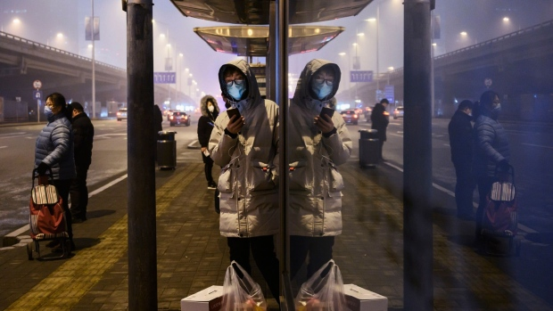 BEIJING, CHINA - FEBRUARY 13: Chinese commuters wear protective masks as they wait for a bus at a usually busy stop on February 13, 2020 in Beijing, China. The number of cases of the deadly new coronavirus COVID-19 rose to more than 52000 in mainland China Thursday, in what the World Health Organization (WHO) has declared a global public health emergency. China continued to lock down the city of Wuhan in an effort to contain the spread of the pneumonia-like disease which medicals experts have confirmed can be passed from human to human. In an unprecedented move, Chinese authorities have maintained and in some cases tightened the travel restrictions on the city which is the epicentre of the virus and also in municipalities in other parts of the country affecting tens of millions of people. The number of those who have died from the virus in China climbed to over 1300 on Thursday, mostly in Hubei province, and cases have been reported in other countries including the United States, Canada, Australia, Japan, South Korea, India, the United Kingdom, Germany, France and several others. The World Health Organization has warned all governments to be on alert and screening has been stepped up at airports around the world. Some countries, including the United States, have put restrictions on Chinese travellers entering and advised their citizens against travel to China. (Photo by Kevin Frayer/Getty Images)