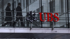 Employees pass between offices as UBS Group AG logo sits on a walkway at the UBS headquarters in Zurich, Switzerland.