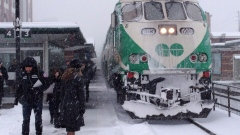 A commuter waits to board a GO train in Oakville, Ont. on Thursday December 11, 2014.