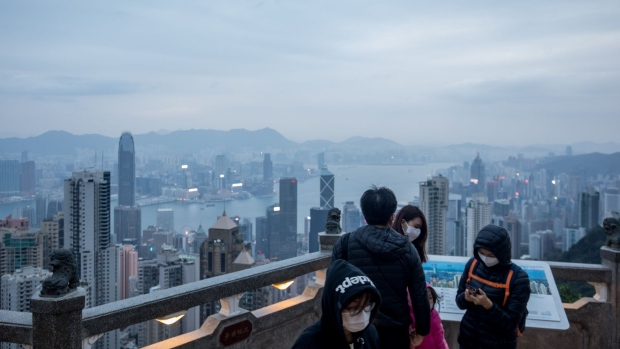 "People wearing protective masks stand on a viewing terrace at Victoria Peak in Hong Kong, China, on Monday, Feb. 3, 2020. The outlook for the Hong Kong economy in 2020 is ""subject to high uncertainties"" including the global economic recovery, U.S.-China trade relations, the ongoing protests and the progression of the viral outbreak, the government said in a release. Photographer: Paul Yeung/Bloomberg"