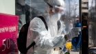 A worker wearing a protective suit wipes disinfectant on the door of a clothing store on Munjeong-dong Rodeo Street in the Songpa district of Seoul, South Korea, on Thursday, Feb. 27, 2020. More coronavirus cases were reported in other countries than in China for the first time, the World Health Organization said, a significant development highlighting the spread of the epidemic around the globe. The U.S. urged travelers to reconsider trips to South Korea as the country's number of cases rose to more than 1,500. Photographer: SeongJoon Cho/Bloomberg