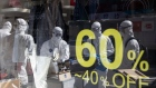 Workers wearing protective suits are reflected in a glass window of clothing store on Munjeong-dong Rodeo Street in the Songpa district of Seoul, South Korea, on Thursday, Feb. 27, 2020. More coronavirus cases were reported in other countries than in China for the first time, the World Health Organization said, a significant development highlighting the spread of the epidemic around the globe. The U.S. urged travelers to reconsider trips to South Korea as the country's number of cases rose to more than 1,500. Photographer: SeongJoon Cho/Bloomberg