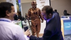 Attendees take a photograph of a man dressed as a copper miner statue at the Chilean Ministry of Mining booth during the 2017 Prospectors & Developers Association of Canada (PDAC) convention in Toronto, Ontario, Canada, on Tuesday, March 7, 2017. The prospect of increased deal-making is set to be a hot topic for the more than 20,000 geologists, promoters and investors expected to attend the four-day PDAC convention, the world's biggest mining gathering. Photographer: Cole Burston/Bloomberg