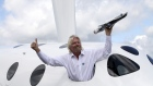 Richard Branson, poses for photographers with a model of the LauncherOne rocket, from the window of Virgin Galactic's SpaceShipTwo, on the third day of the Farnborough International Air Show in Farnborough, U.K., on Wednesday, July 11, 2012. The Farnborough International Air Show runs from July 9-15. Photo: Bloomberg Photographer: Bloomberg/Bloomberg