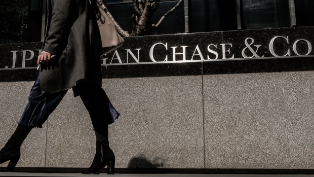Pedestrians pass in front of a JPMorgan Chase & Co. office building in New York. Photographer: Christopher Lee/Bloomberg