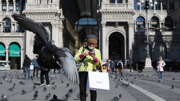 MILAN, ITALY - FEBRUARY 28: A pigeon flies over a woman wearing a protective mask in the Duomo Square on February 28, 2020 in Milan, Italy.