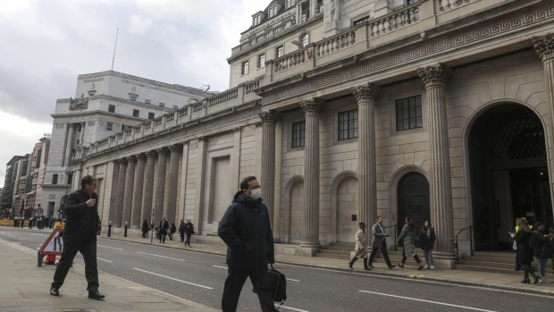 A pedestrian wearing a protective face mask walks past the the Bank of England, in the City of London, U.K., on Tuesday, March 3, 2020. Andrew Bailey's tenure as BOE Governor starts when concerns about the coronavirus have sparked a flurry of speculation that central banks around the world will start emergency policy easing. Photographer: Simon Dawson/Bloomberg