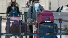 Passengers wear masks as they arrive for their flight at Pearson Airport in Toronto on Friday, March