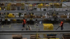 Employees pull carts containing online orders at the Amazon.com Inc. fulfillment center in Robbinsville, New Jersey.