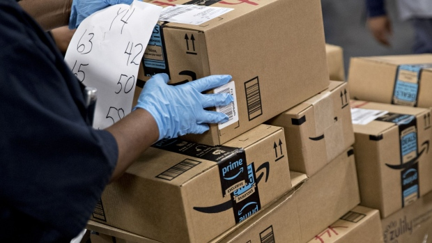 An employee arranges Amazon.com Inc. packages before delivery at the United States Postal Service (USPS) Joseph Curseen Jr. and Thomas Morris Jr. processing and distribution center in Washington, D.C., U.S., on Tuesday, Dec. 12, 2017. The USPS said it expects to deliver over 15 billion total pieces of mail this holiday season with expanded Sunday delivery operations in certain areas, delivering over six million packages each Sunday in December. Photographer: Andrew Harrer/Bloomberg