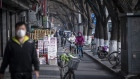 Commuters wearing protective masks ride bicycles down a street in Beijing on March 18. Photographer: Qilai Shen/Bloomberg