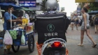 An Uber Technologies Inc. Eats delivery driver rides a motorcycle along a road in Bangkok, Thailand, on Friday, March 9, 2018. Uber Chief Executive Officer Dara Khosrowshahi said growth of the UberEats app was exploding and estimated that it would be the largest food-delivery business in the world this year. Photographer: Brent Lewin/Bloomberg