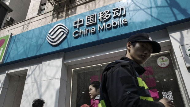 Pedestrians walk past a China Mobile Ltd. store in Shanghai, China, on Tuesday, March 21, 2017. China Mobile is scheduled to release full-year earnings results on March 23. Photographer: Qilai Shen/Bloomberg