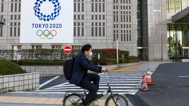 A cyclist passes banners for the Tokyo 2020 Olympic and Paralympic Games on March 24. Photographer: Noriko Hayashi/Bloomberg