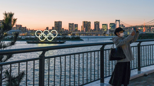 A person takes a photo of floating Olympic rings installed near Odaiba island, Tokyo on March 24. Photographer: Noriko Hayashi/Bloomberg