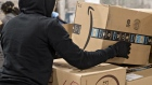 An employee moves an Amazon.com Inc. package for delivery at the United States Postal Service (USPS) Joseph Curseen Jr. and Thomas Morris Jr. processing and distribution center in Washington, D.C., U.S., on Tuesday, Dec. 12, 2017.