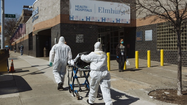 Paramedics wearing protective equipment carry a stretcher into Elmhurst Hospital Center in the Queens borough of New York, U.S., on Thursday, March 26, 2020. New York City is the epicenter of the coronavirus pandemic in the United States, putting historic pressure on a world-renowned healthcare system as the number of confirmed cases in the area grows exponentially. Photographer: Angus Mordant/Bloomberg
