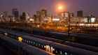 Commercial office buildings stand illuminated on the city skyline beyond trains at the Johannesburg Park railway station in the central business district of Johannesburg, South Africa, on Tuesday, Aug. 8, 2019. Eskom Holdings SOC Ltd., South Africa's biggest polluter, said emissions of particulate matter that cause chronic respiratory disease are at their highest level in two decades as the state power utility's financial meltdown has seen it skip maintenance and has triggered strikes. Photographer: Waldo Swiegers/Bloomberg