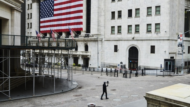A pedestrian films himself while walking past the New York Stock Exchange (NYSE) on a nearly empty Wall Street in the Financial District of New York, U.S., on Monday, March 30, 2020. Roughly 37,500 people have tested positive for the coronavirus in New York City, officials said on Monday, up about 3,700 from a day earlier. Photographer: Gabby Jones/Bloomberg