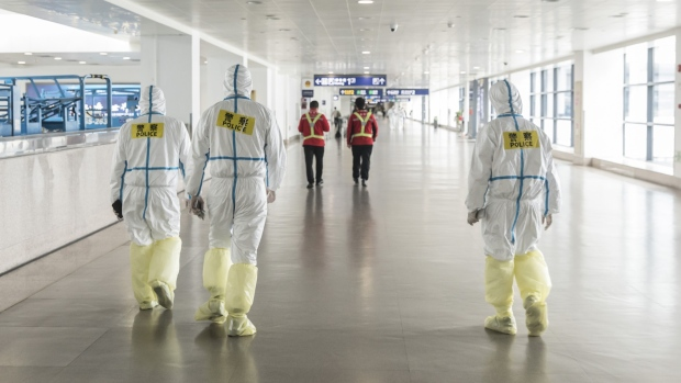 Airport employees wear full body protective suits at Pudong International Airport in Shanghai