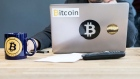 An employee uses a laptop computer branded with bitcoin logos inside the offices of La Maison du Bitcoin bank in Paris, France. Photographer: Chritophe morin/Bloomberg