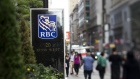 Pedestrians pass in front of RBC Royal Bank signage outside the company's office in this photo taken with a tilt-shift lens near Bay Street in Toronto. Photographer: Brent Lewin/Bloomberg