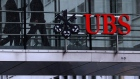 Employees pass between offices as UBS Group AG logo sits on a walkway at the UBS headquarters in Zurich, Switzerland, on Monday, Jan. 22, 2018. A UBS loan backed by shares of Steinhoff International Holdings NV was to blame for the majority of the Swiss banks 79 million francs ($82 million) in credit losses in the fourth quarter, a person with knowledge of the matter said. Photographer: Stefan Wermuth/Bloomberg