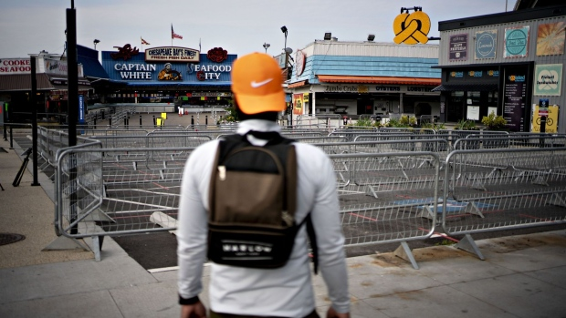 A pedestrian stands outside the temporarily closed fish market in The Wharf neighborhood of Washington, D.C. on April 7. Photographer: Andrew Harrer/Bloomberg