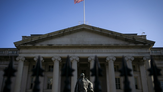 An American flag flies above the U.S. Treasury building in Washington. Photographer: Al Drago/Bloomberg