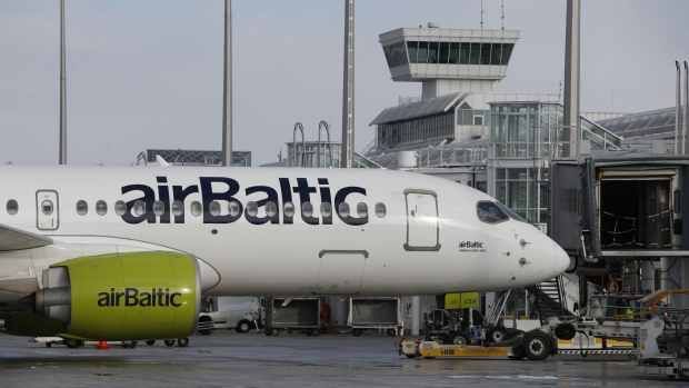 A passenger aircraft operated by Air Baltic Corp AS stands at a passenger boarding gate at Munich airport in Munich, Germany, on Tuesday, Jan. 29, 2019. Deutsche Lufthansa AG has decided to speed up growth at Munich and develop it into a hub with a focus on Asia. Photographer: Michaela Handrek-Rehle/Bloomberg