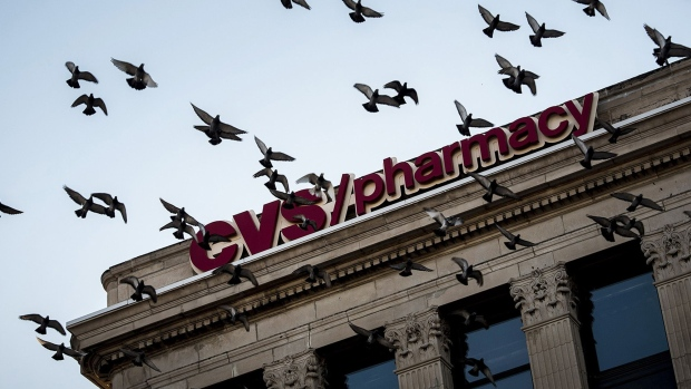 Birds fly past CVS Health Corp. signage in Chicago, Illinois. Photographer: Christopher Dilts/Bloomberg