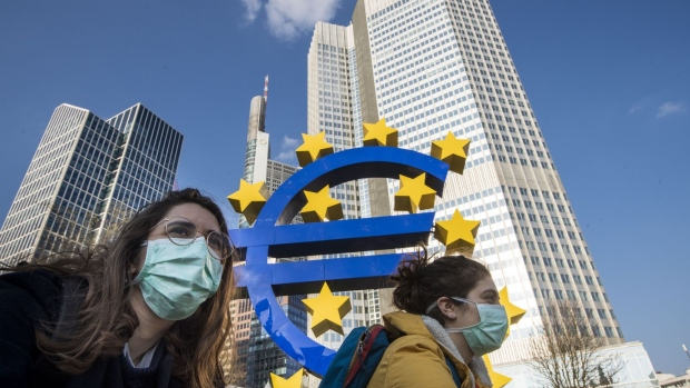 FRANKFURT AM MAIN, GERMANY - MARCH 19: Two students wear face mask while they pass the Euro sculpture with bicycles in the finance district on March 19, 2020 in Frankfurt, Germany.
