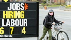 A woman checks out a jobs advertisement sign during the COVID-19 pandemic in Toronto
