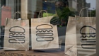 An employee wearing a protective mask picks up a take-out order at Shake Shack. Photographer: Andrew Harrer/Bloomberg