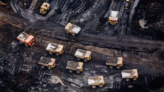 Heavy haulers are seen at the Suncor Energy Inc. Fort Hills mine in this aerial photograph taken above the Athabasca oil sands near Fort McMurray, Alberta, Canada, on Monday, Sept. 10, 2018. While the upfront spending on a mine tends to be costlier than developing more common oil-sands wells, their decades-long lifespans can make them lucrative in the future for companies willing to wait. Photographer: Ben Nelms/Bloomberg