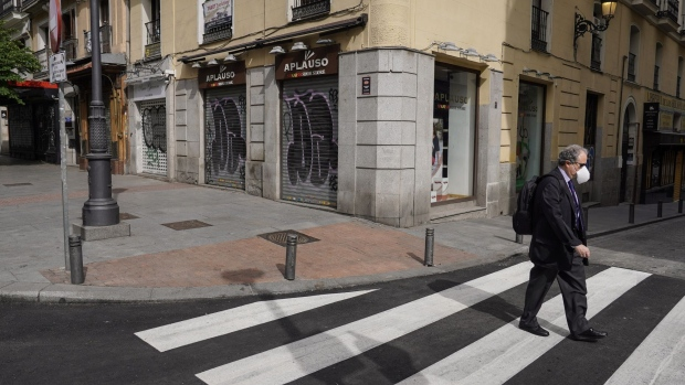 A commuter wearing a protective face mask uses a pedestrian crossing as shuttered stores line the street beyond in Madrid, Spain, on Thursday, May 7, 2020.