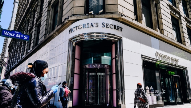 Pedestrians wearing protective masks pass in front of a Victoria's Secret Stores LLC store, a subsidiary of L Brands Inc., in Herald Square in New York, U.S., on Tuesday, May 5, 2020. Photographer: Nina Westervelt/Bloomberg