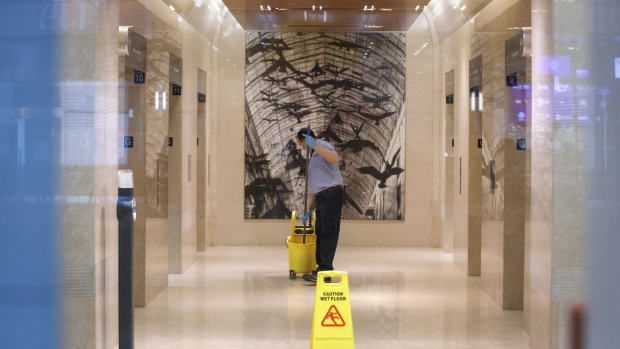 A worker cleans an office tower lobby in Toronto, Ontario, Canada, on Wednesday, March 25, 2020. The unemployment rate in Ontario, which accounts for almost 40% of Canada's output, was running at close to a record low before the province ordered all but essential businesses to shut down in a bid to contain the virus. Ontario now sees zero growth for this year. Photographer: Cole Burston/Bloomberg