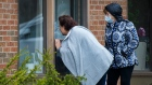 Two sisters visit their mother through the window at a seniors retirement residence in Mississauga