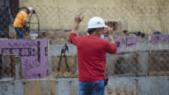 A worker holds on to a fence at a low-income housing construction site in Schenectady