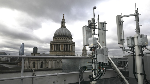 A Huawei Technologies Co. logo sits on 5G equipment, bottom center, alongside 5G masts installed on a rooftop overlooking St. Paul's Cathedral during trials by EE the wireless network provider, owned by BT Group Plc, in the City of London, U.K., on Friday, March 15, 2019. Europe would fall behind the U.S. and China in the race to install the next generation of wireless networks if governments ban Chinese equipment supplier Huawei Technologies Co. over security fears, according to an internal assessment by Deutsche Telekom AG. Photographer: Simon Dawson/Bloomberg