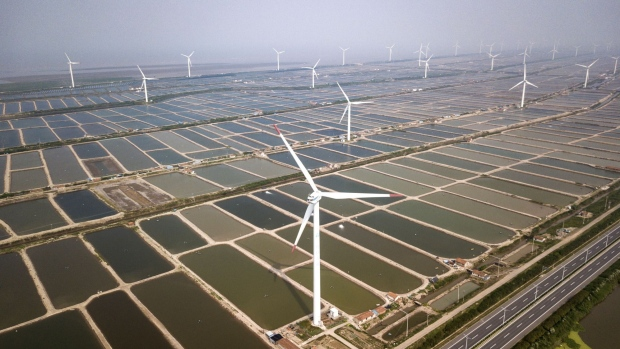 Wind turbines manufactured by Shanghai Electric Group Co. stand at a wind farm operated by China Huaneng Group in this aerial photograph taken in Qidong, China, on Thursday, June 7, 2018. China, the world's largest wind power producer, is considering setting a national target to reduce average wind curtailment rates to less than 10 percent next year and to about 5 percent by 2020, according to an April 12 government policy proposal document. Photographer: Qilai Shen/Bloomberg