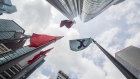 The corporate flag for Hong Kong Exchanges & Clearing Ltd. (HKEX), right, and the Chinese flag, left, fly outside the Exchange Square complex in Hong Kong, China, on Monday, Sept. 16, 2019. The Hong Kong bourse's unsolicited takeover bid for the London Stock Exchange Group Plc was greeted with a scathing rejection and the exchange suffered a further humiliation when China praised the rebuff as well. Photographer: Paul Yeung/Bloomberg
