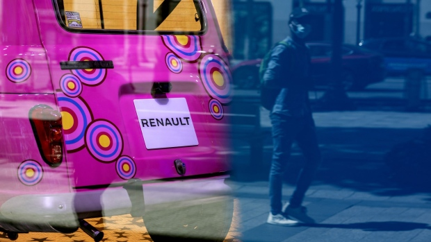 A pedestrian wearing a protective face mask is reflected in a window of the Renault flagship showroom in Paris. Photographer: Adrienne Surprenant/Bloomberg
