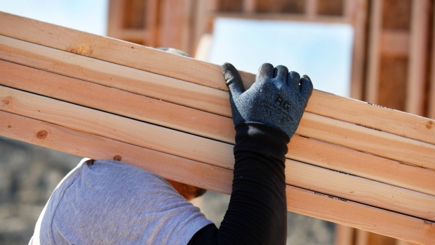 A worker carries lumber during the construction of a home in Lindon