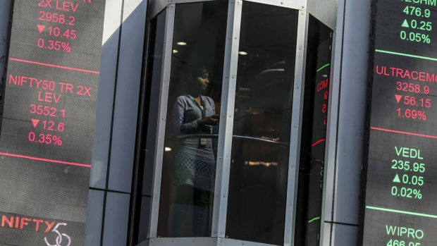 An elevator travels next to electronic boards displaying stock figures at the National Stock Exchange of India Ltd. (NSE) building in Mumbai, India, on Friday, Dec. 16, 2016. The NSE plans to file a draft prospectus this month for an initial public offering of about 100 billion rupees ($1.5 billion), pushing ahead with the nation's biggest listing in more than six years after its top executive resigned, people with knowledge of the matter said. Photographer: Dhiraj Singh/Bloomberg
